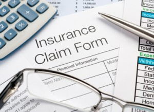 Insurance Claim Form with pen and calculator